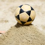 this picture shows a footvolley ball in the sand.